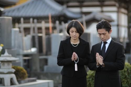 お墓で手を合わせr喪服のカップル